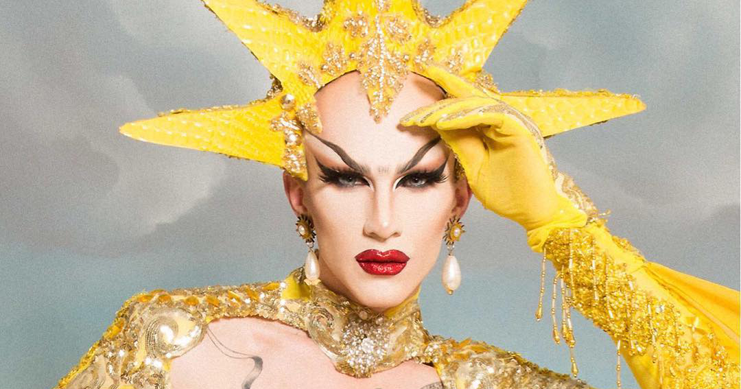 Sasha Velour wears a yellow crown and yellow gloves.