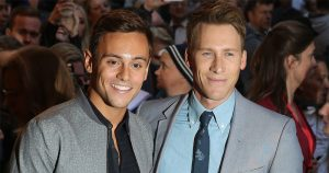Tom Daley and Dustin Lance Black pose for press shots at a public event