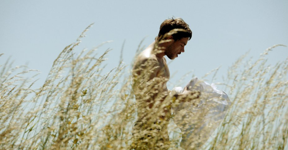 Sauvage star stands shirtless in a field.