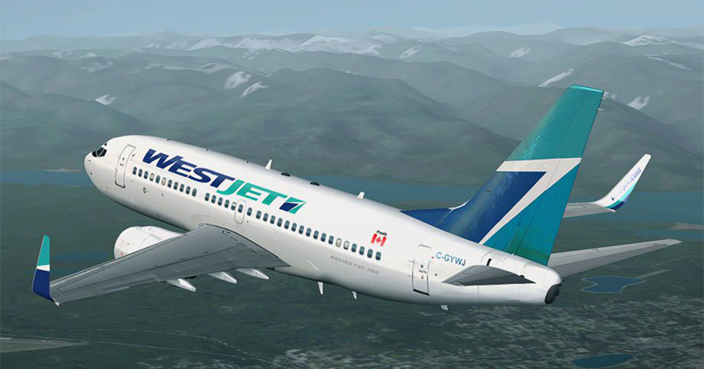 A WestJet passenger plane flies over mountains