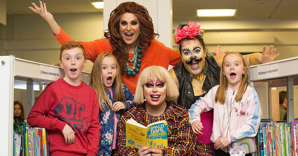 Three drag queens pose with three children in the centre of a library at the Story Time event