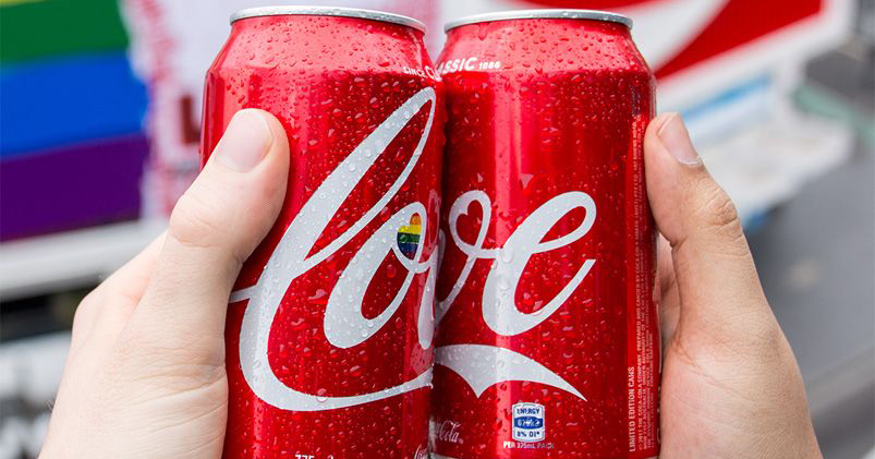 Two cans of Coca Cola held together so their logos read 'love'