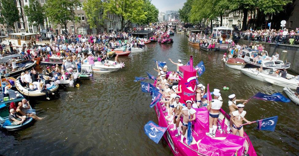 A pride float goes down the canal in Amsterdam, one of the safest places for queer travellers to visit