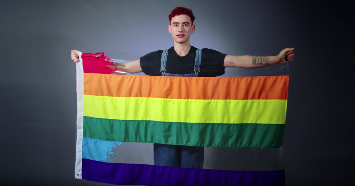 Image of Olly Alexander holding Pride Flag with the red and blue stripes ripped out.