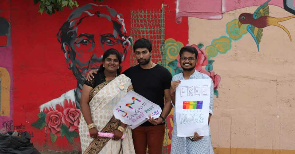 Three people in India hold placards offering free hugs.