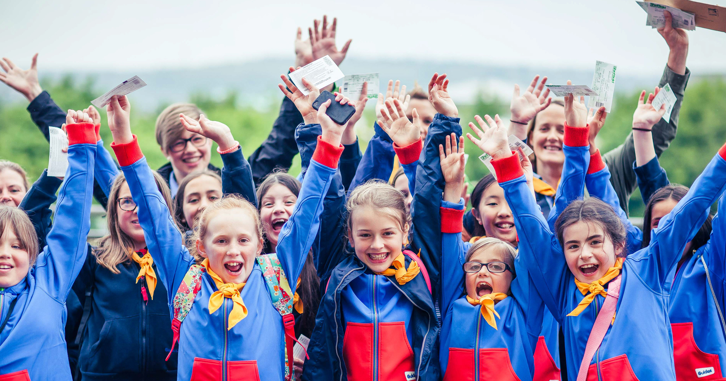 A group of young scouts cheering at a girlguiding event