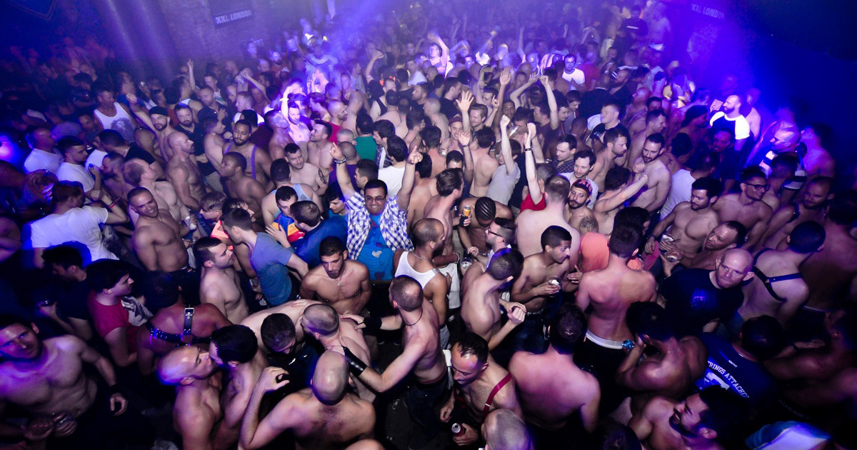 A crowd of topless men dancing inside the London club XXL