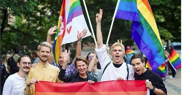 Image of Zabarauskas with friends holding Pride flags at Gay Pride following arson attacks.