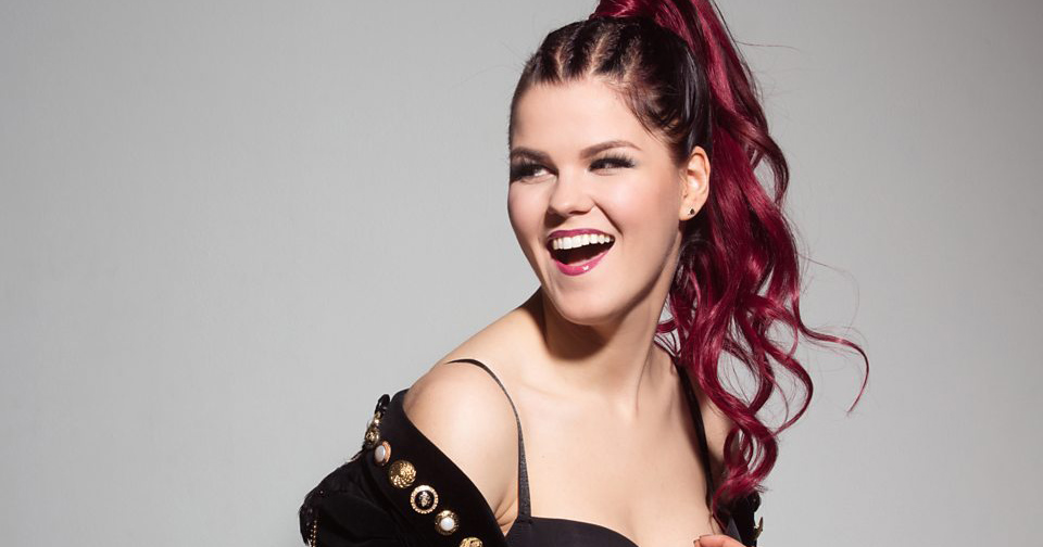 Saara Aalto laughing with hair tied up wearing an off the shoulder outfit