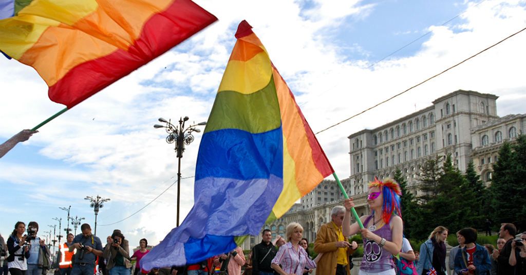 Girl waves rainbow flag at Bucharest Pride in Romania