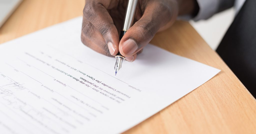 A person signing their will. CFI encourages people to leave charitable gifts in their wills.