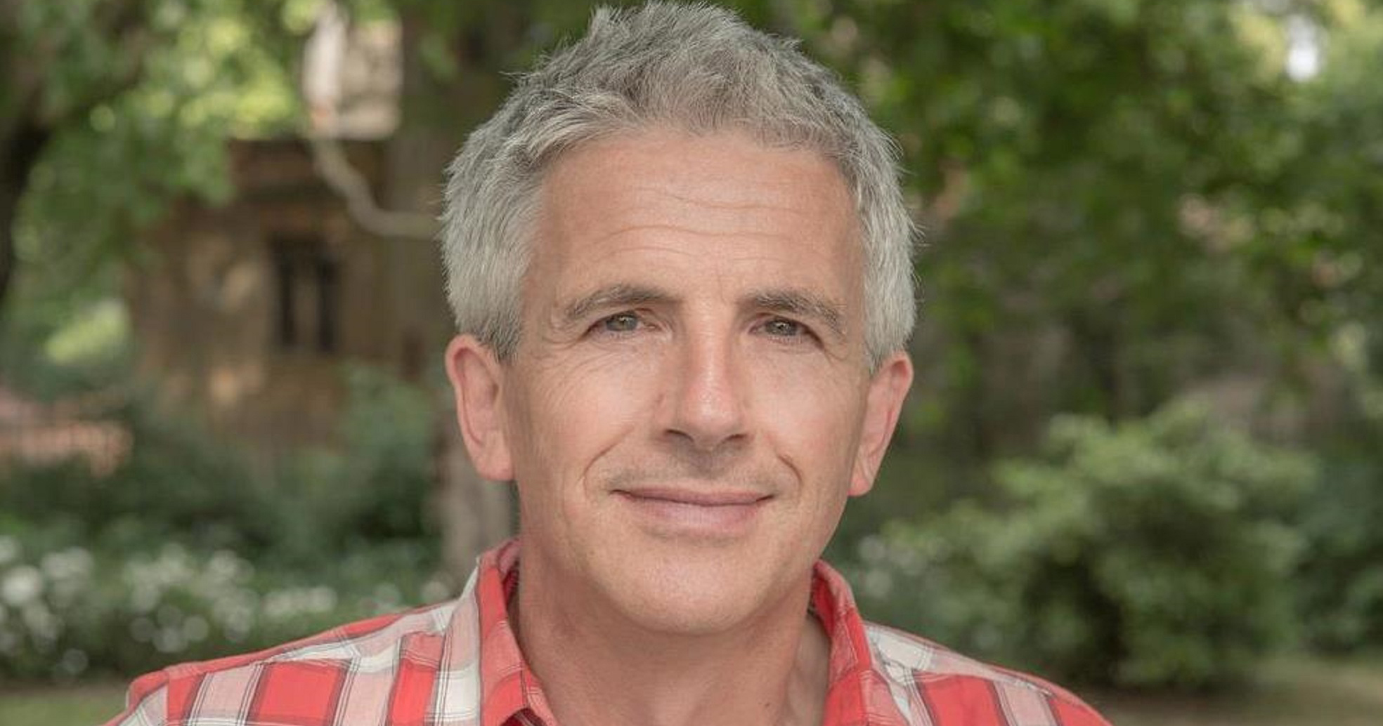Headshot of author Patrick Gale with trees in the background
