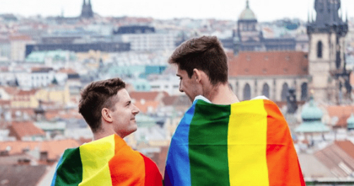 Image of two men wearing pride flags overlooking Prague in the Czech Republic.