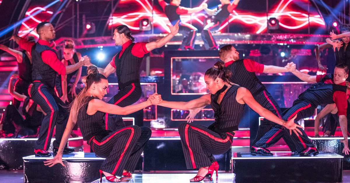 A group of 12 of the Strictly Come Dancing professionals performing same-sex dance routines while dressed in pinstripe suits