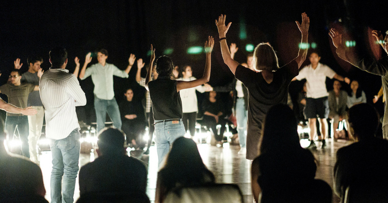 The audience at theatre show The Fever all standing with their hands in the air
