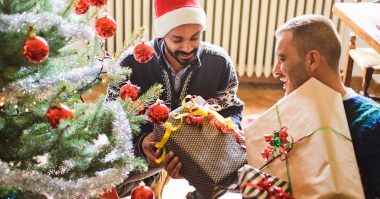 Gay couple celebrating Christmas by exchanging gifts by the Christmas tree