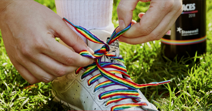 Image of someone tying rainbow laces into their boots.