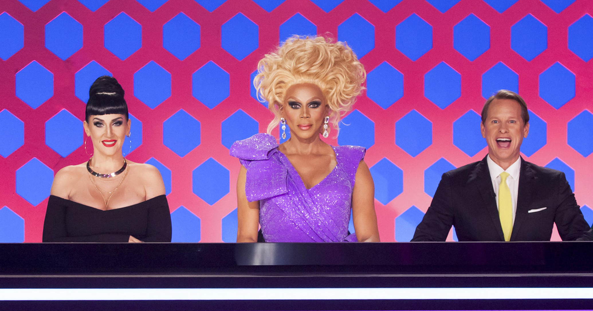 Michelle Visage, RuPaul and Carson Kressley, the judges from Ru Pul's Drag Race, sit behind their desk