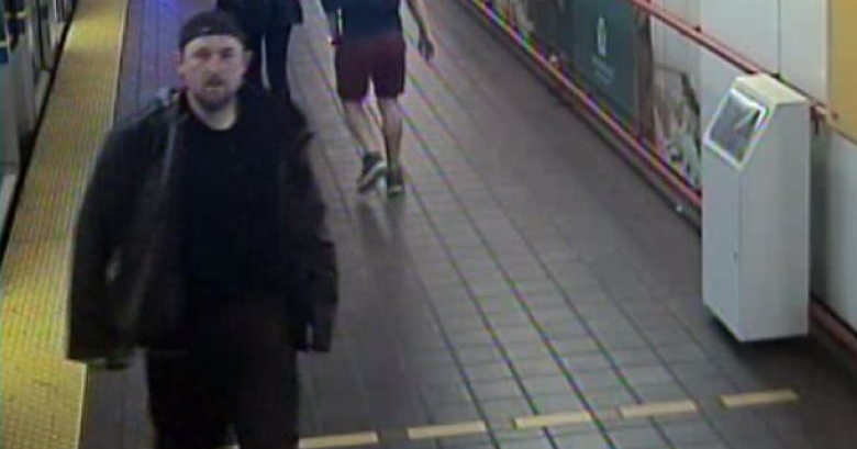 CCTV image of suspected the suspected serial attacker dressed in black in a subway station