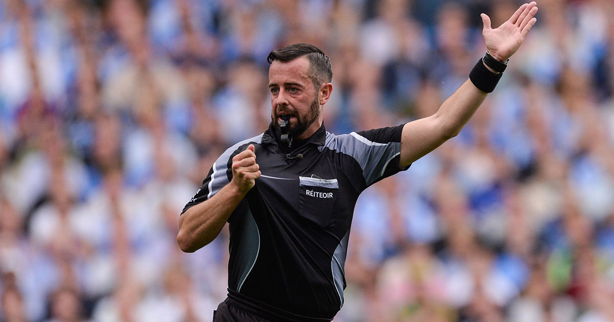 David Gough refereeing at a GAA match in Croke Park with hand up and blowing a whistle
