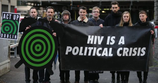 "Activists from ACT UP hold up a banner that reads ""HIV is a Political Crisis"" as they address the HIV crisis in Ireland."
