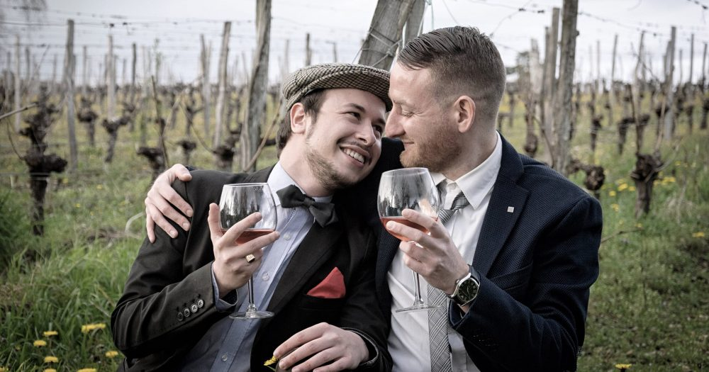 A gay couple rinking wine on their honeymoon in Ireland, looking into each other's eyes.