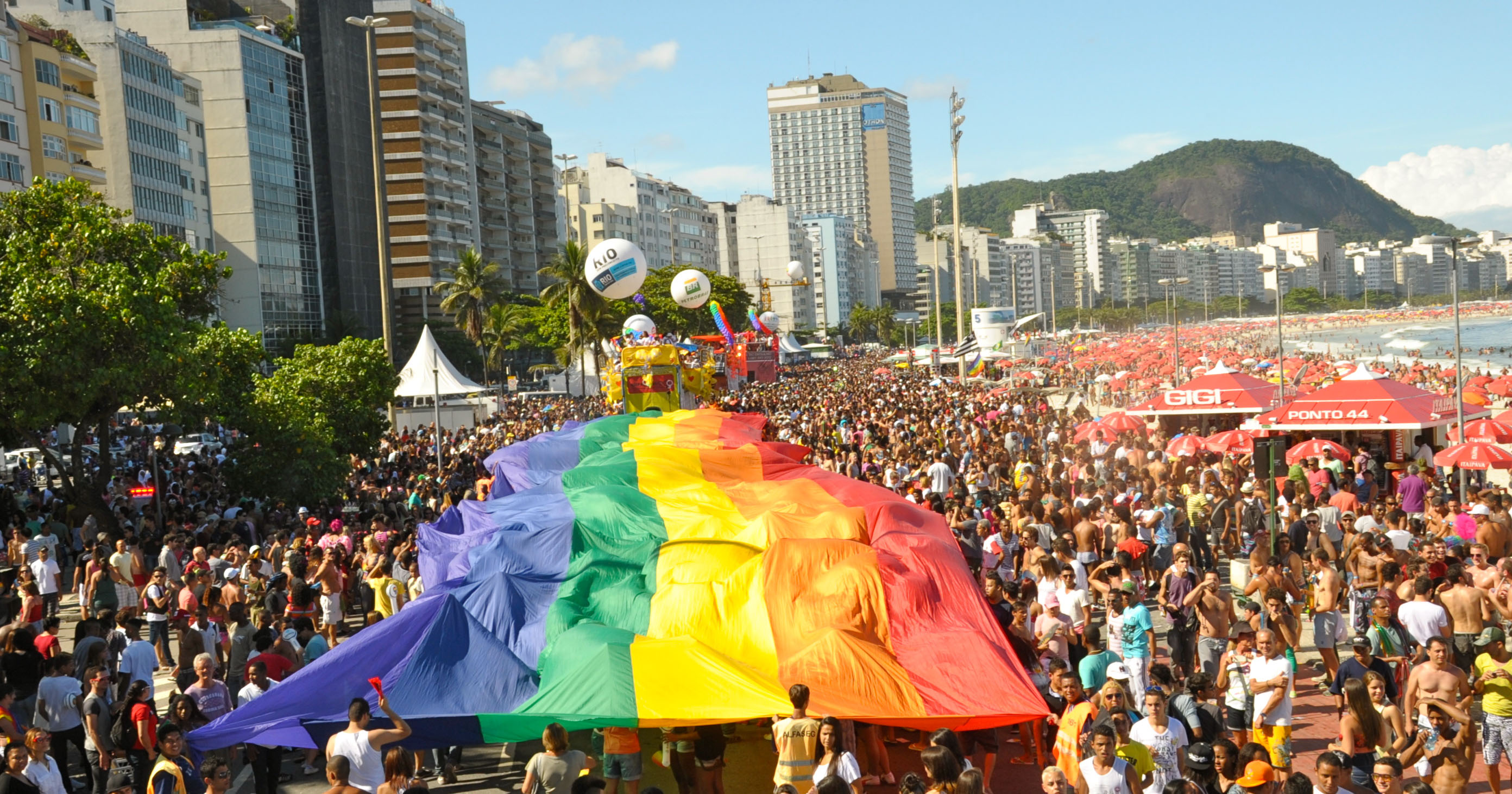 Hundreds of Brazilians on the beach in Rio carrying a huge Pride flag
