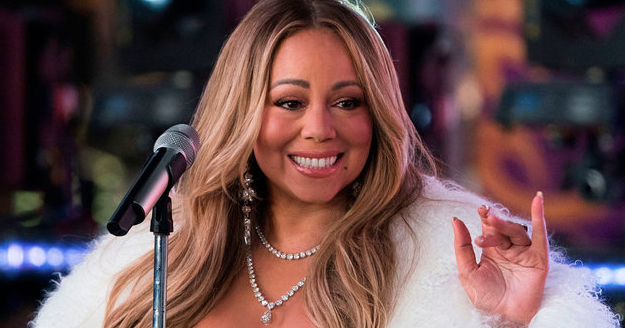 Mariah Carey waving at fans in front of a microphone.