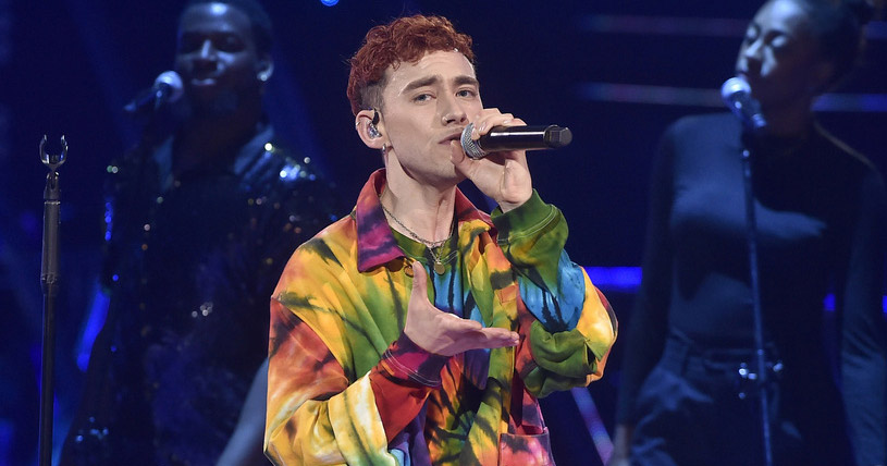 Olly Alexander singing on The Voice Of Poland dressed in rainbows