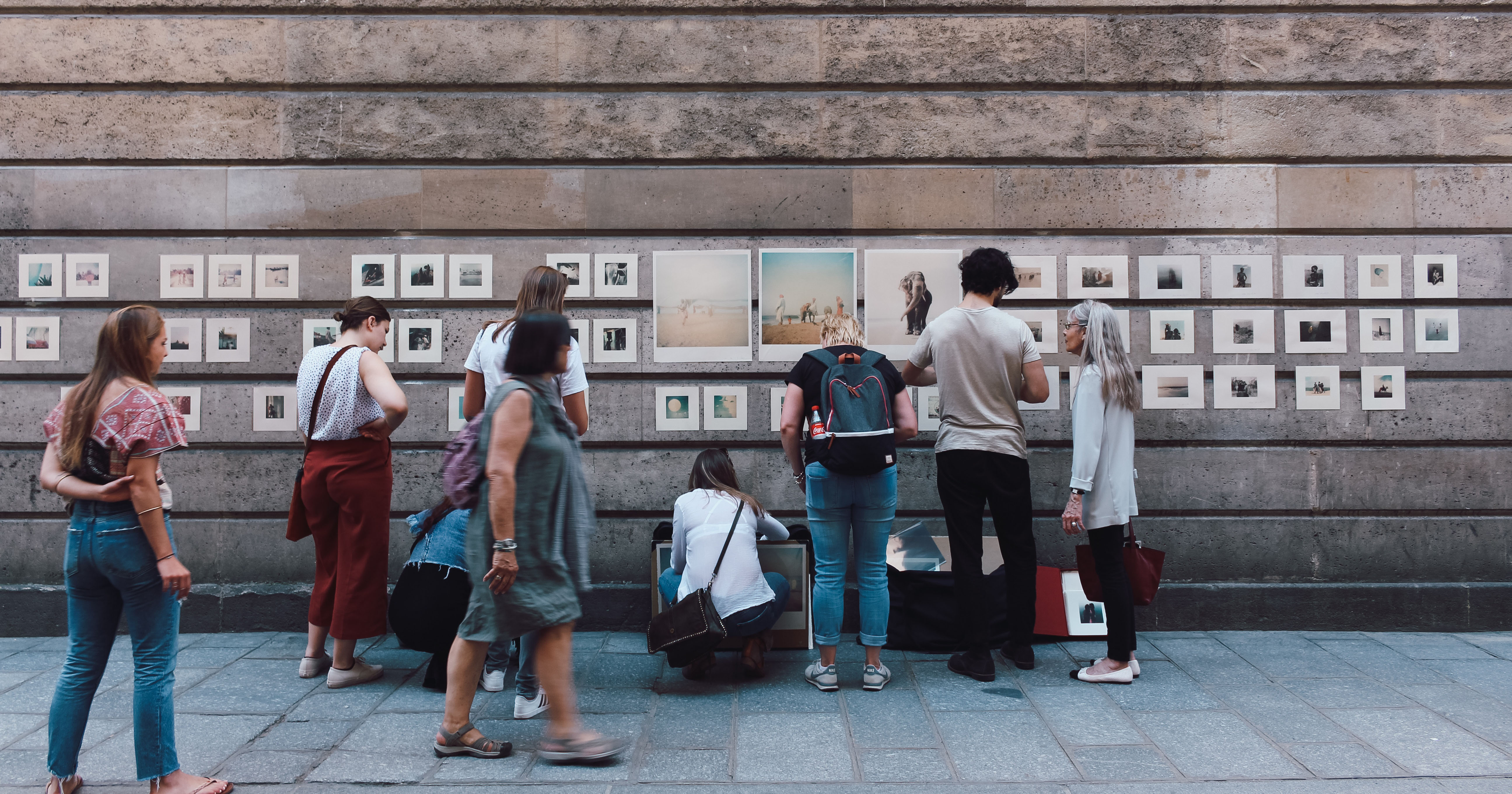 A photovoice exhibition with a group of people all staring at photos pinned to a wall
