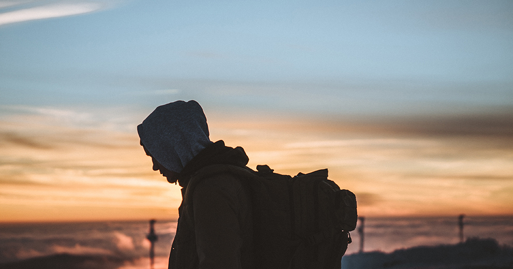 An image representing youth homelessness featuring a young man with a backpack in silhouette against the evening sky