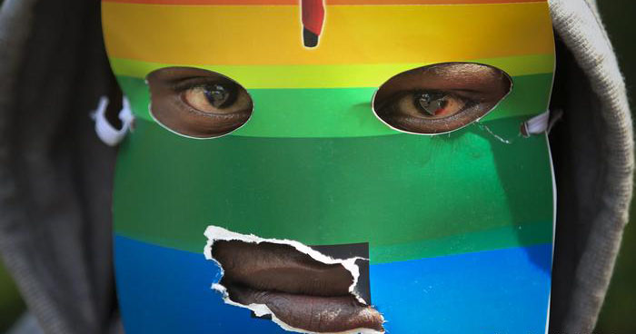 An African man with his hood up covers his face with a paper rainbow mask