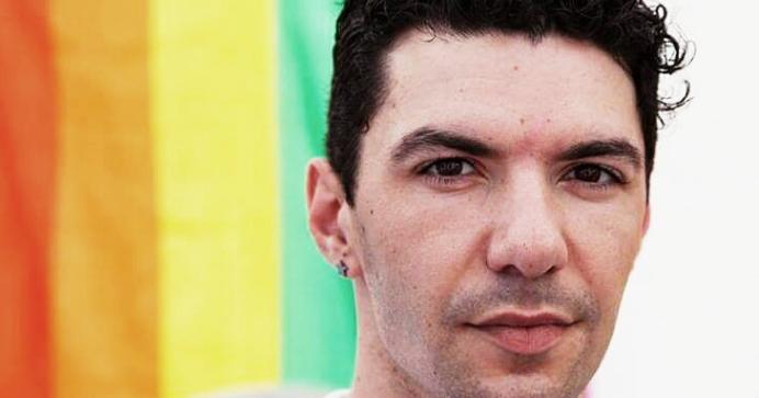 Photo of Zak Kostopoulos against a rainbow flag.