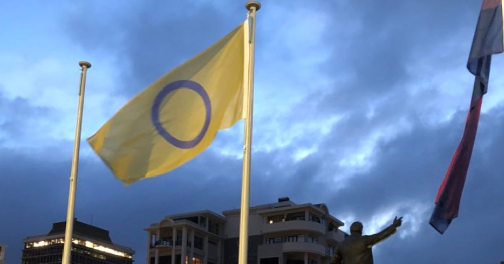 A flag representing intersex people sways in the wind.