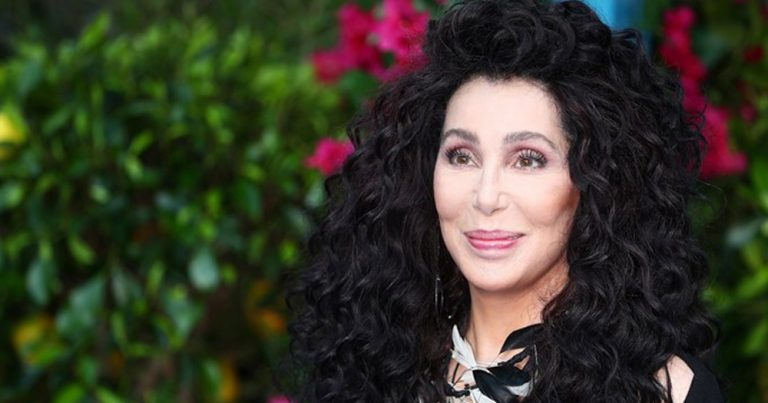 Cher standing in front of a bush.