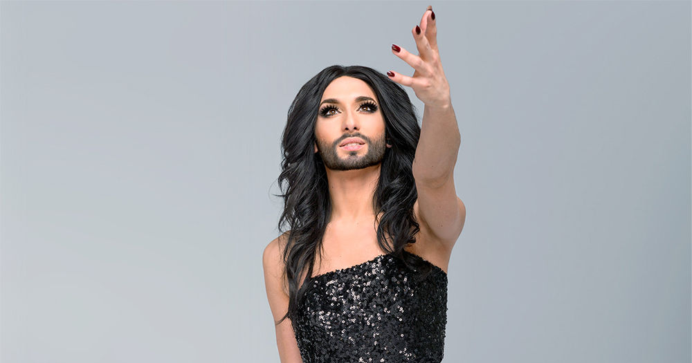 Conchita Wurst looks into the distance, hand outstretched