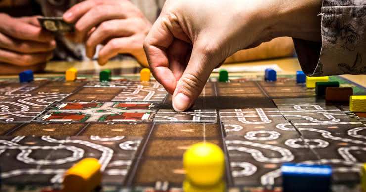 Image of a hand moving a piece on a board game.
