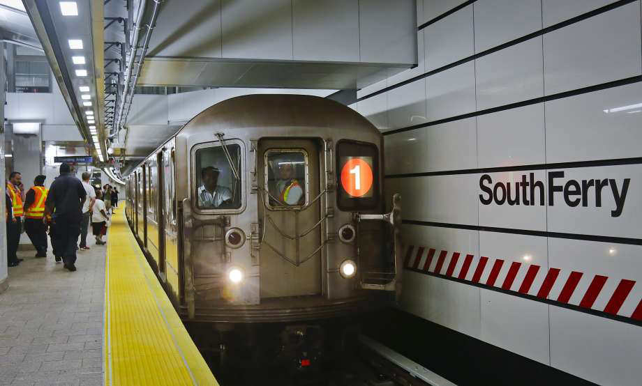 A train pulling into a New York subway station with passengers on the platform