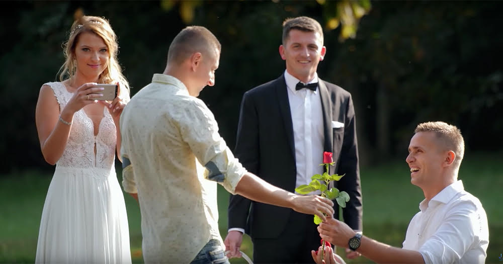 A bride films one of Jakub and David's proposals in a park.