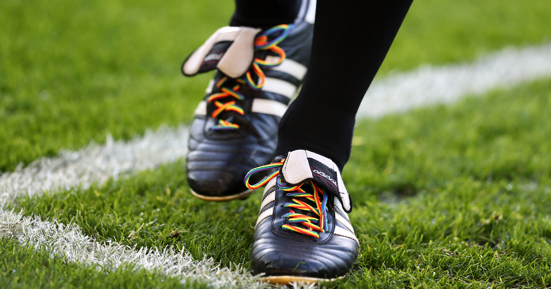 The feet of a Premier League footballer with rainbow laces in their boots