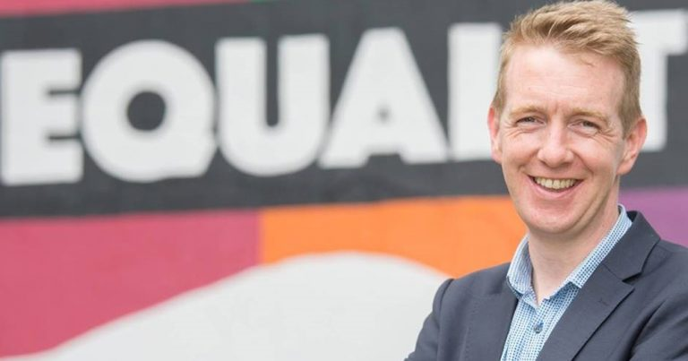 Photo of Tiernan Brady in front of an Eqaulity banner.