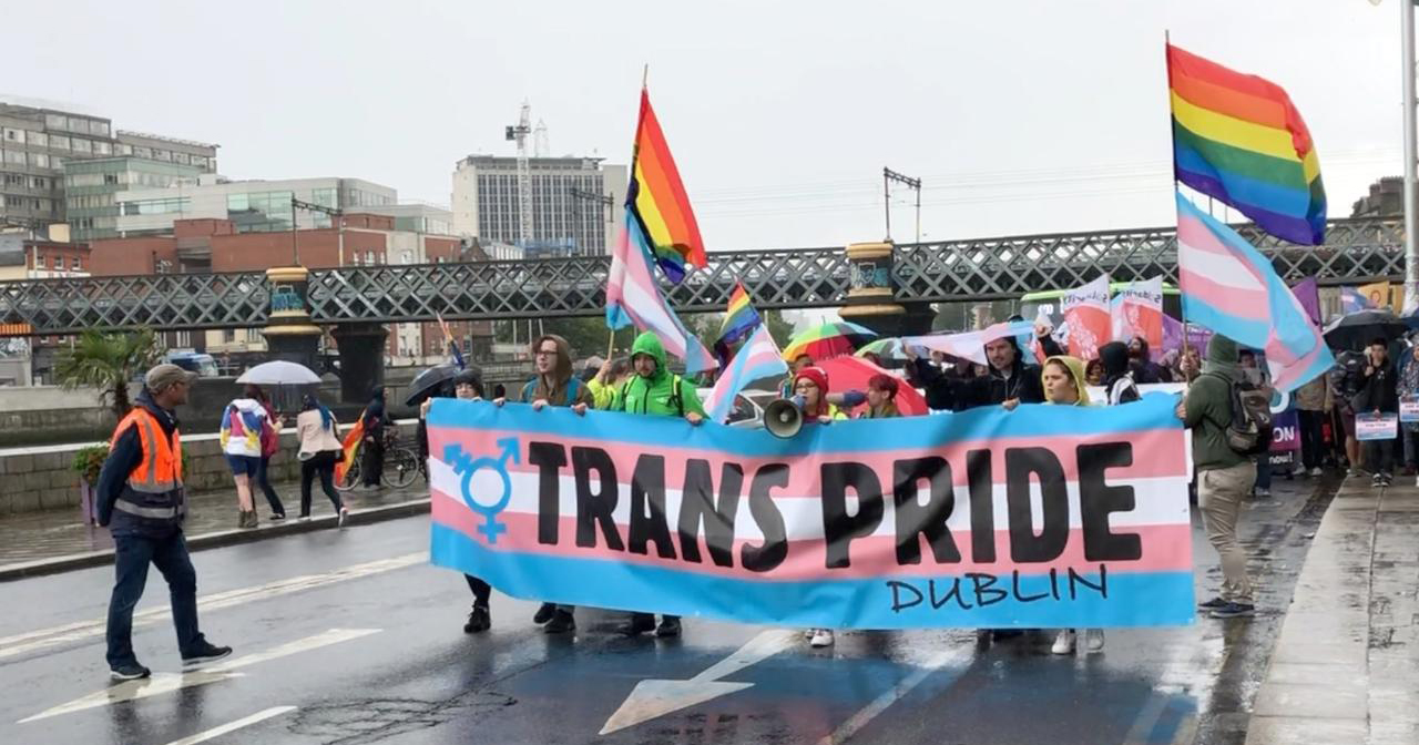 Members of the trans community marching through Dublin holding Trans Pride banners
