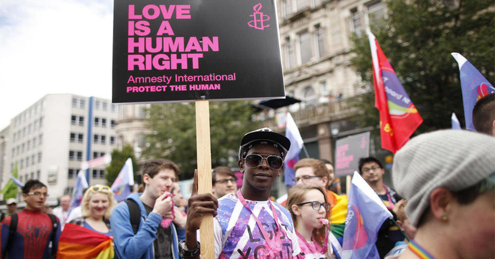 Young activists at an equal marriage march hold Amnesty International signs reading 'Love is a human right'