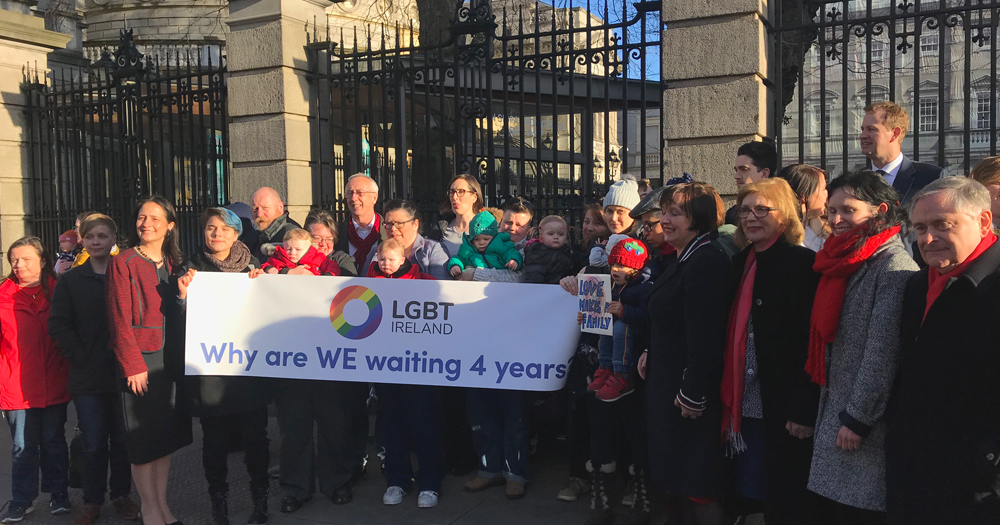 "LGBT families demonstrating outside Leinster House holding up a sign that reads, ""Why are we waiting 4 years?"""