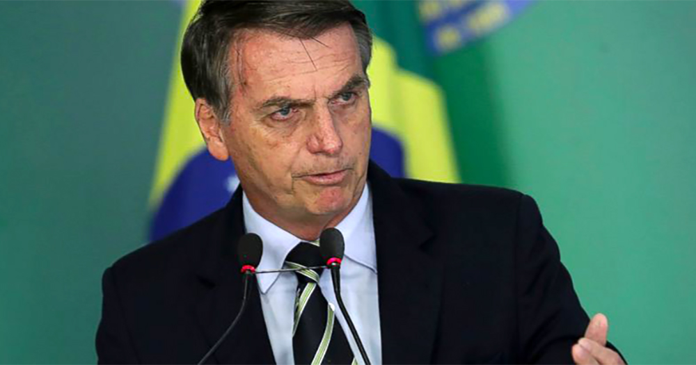 Jair Bolsonaro, behind him a flag of Brazil