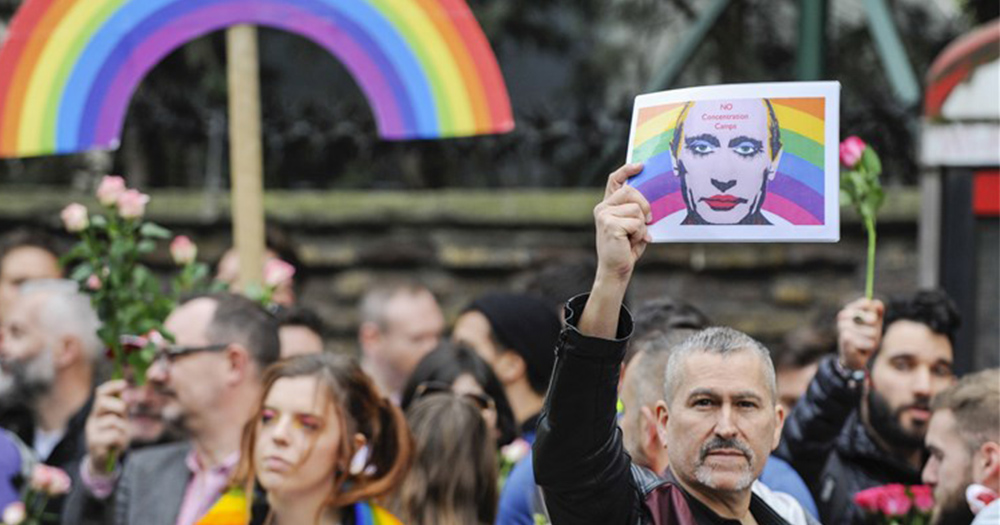 A man holds up an image of Putin wearing makeup with a rainbow behind him as part of a protest against Chechnya LGBT human rights violations