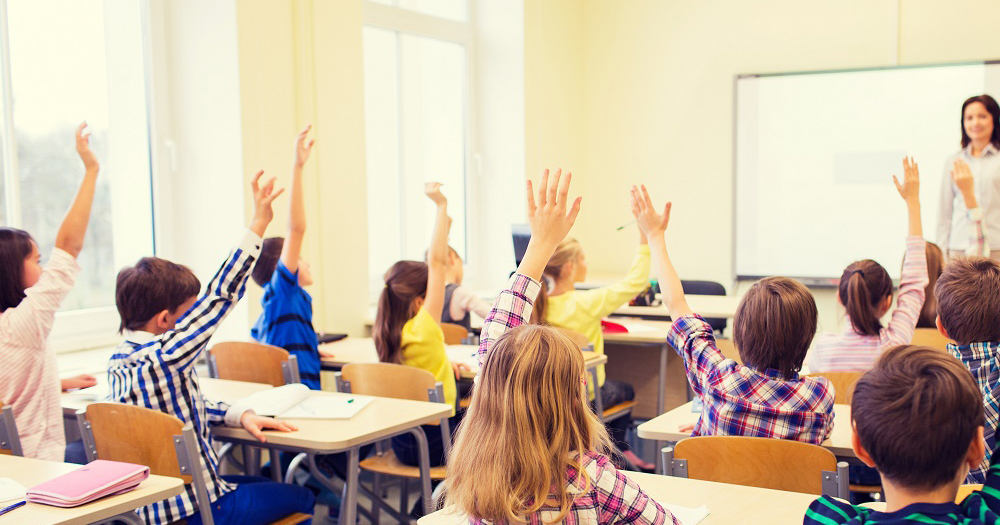 Young students raise their hands to ask their teacher a question in the classroom.