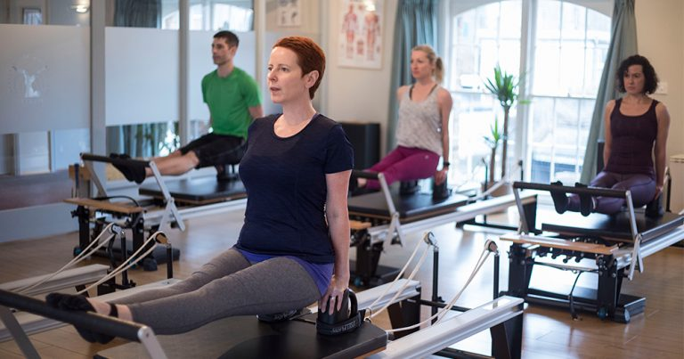 A Pilates teacher leads three of her students through a class