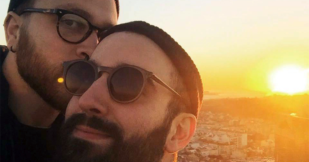 Two men Murillo and Benjamin kissing, behind them a sunset