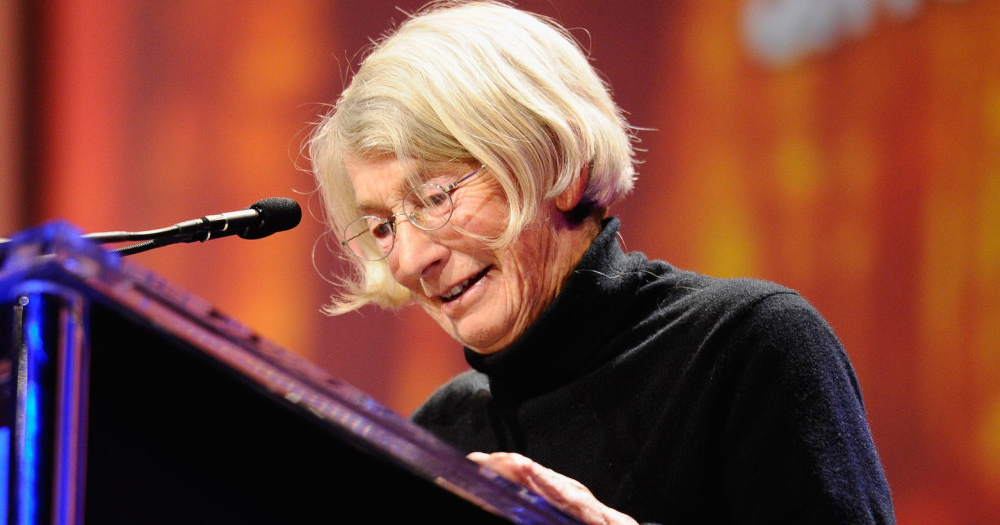 Mary Oliver making a speech looking at notes at a microphone.